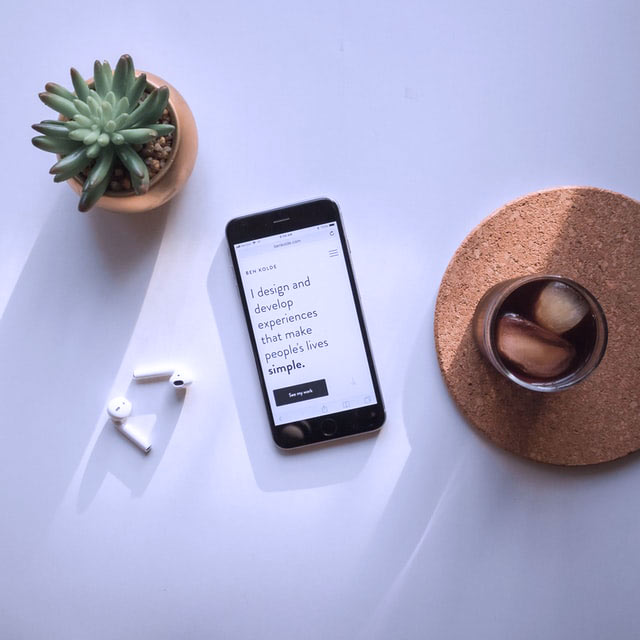 image of a mobile phone face up on a grey table, with a cactus and an ice cold drink on a cork coaster. The mobile screen displays the words I design & develop experiences that make peoples lives simple.